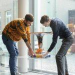Medewerkers van het museum plaatsen voorzichtig een object voor het raam van het museum - Keramiek in quarantaine - foto Ben Nienhuis